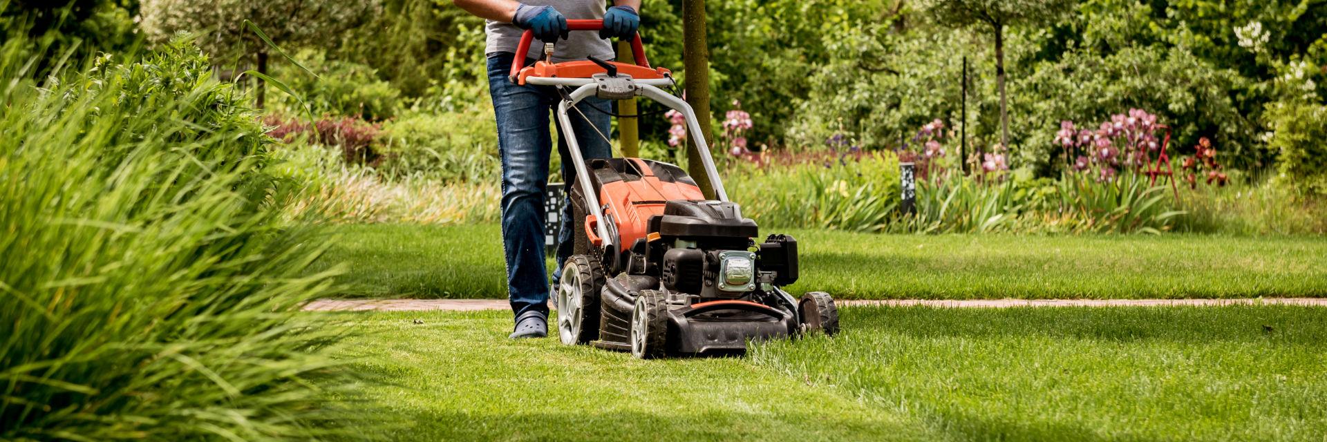 A landscaper mowing a lawn