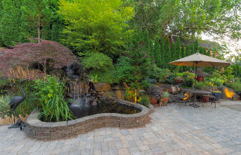a landscaped garden with patio and water features